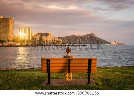 Young woman enjoying Honolulu views from Ala Moana Beach Park - stock photo
