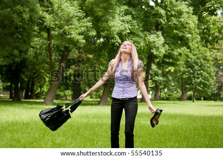 Young woman enjoying life outdoors - spinning around and holding bag and shoes - stock photo