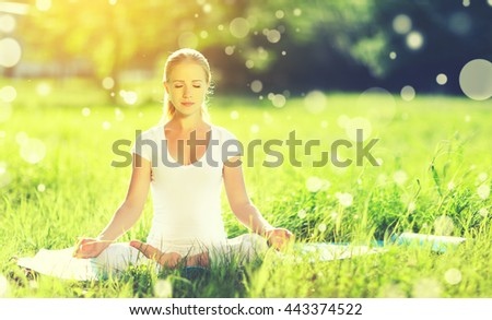 young woman enjoying meditation and yoga on green grass in the summer on nature
