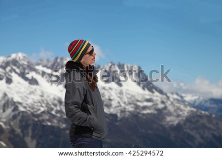 Young woman enjoying mountains view from the top - stock photo