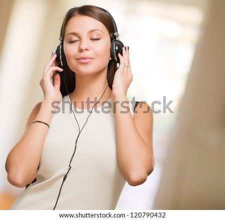 Young Woman Enjoying Music against an abstract background - stock photo