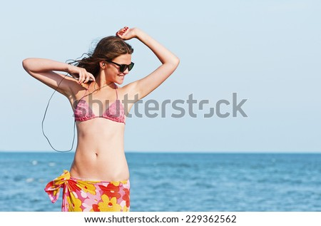 Young woman enjoying music on the beach