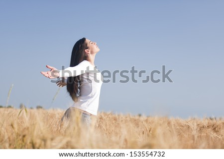 Young woman enjoying nature, arms raised - stock photo