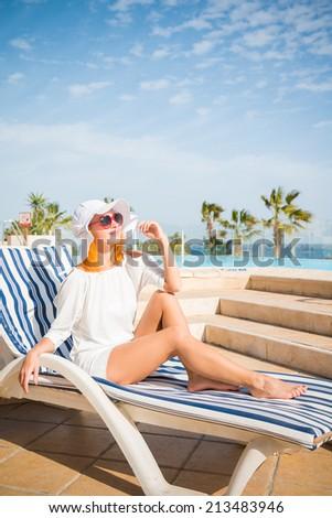 Young woman enjoying sun on sunbed at tourist resort - stock photo