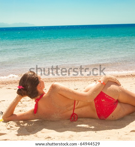 Young woman enjoying sunny day on tropical beach - stock photo