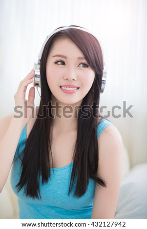 Young woman enjoying the music and relax sit at home, asian beauty - stock photo