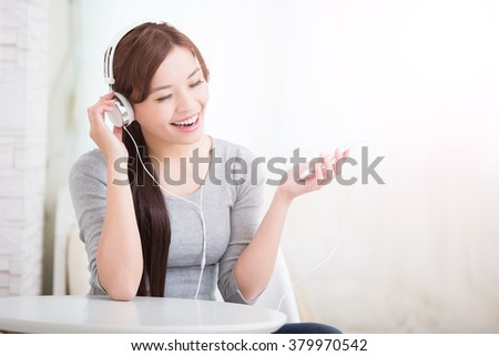 Young woman enjoying the music by smart phone and relax sit at home, asian beauty