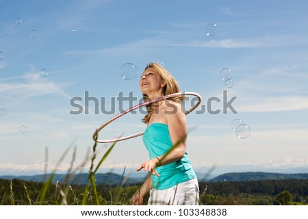 Young woman enjoying the sun in front of a beautiful countryside with tires and bubble