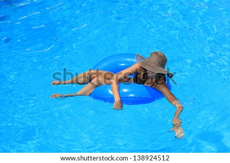 Young woman enjoying the swimming pool in the summertime