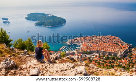 young woman enjoying the view of the Dubrovnik Old Town, sitting on the mountain above the city, Croatia