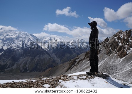 Young woman enjoys spectacular view to high mountains - stock photo