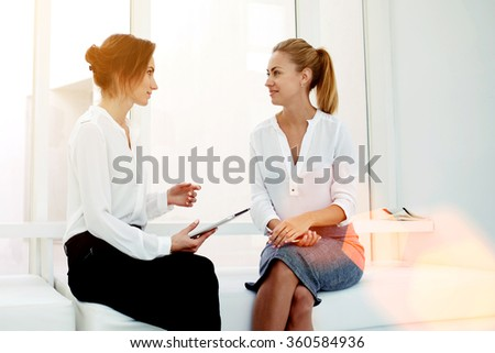 Young woman entrepreneur hold touch pad while telling something to her partner during business meeting, two female confident proud CEO discussing new project while sitting in modern office interior  - stock photo