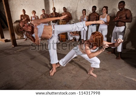 Young woman evades a kick during a Capoeira demonstration