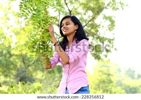 Young woman examine Neem Tree leaf - stock photo