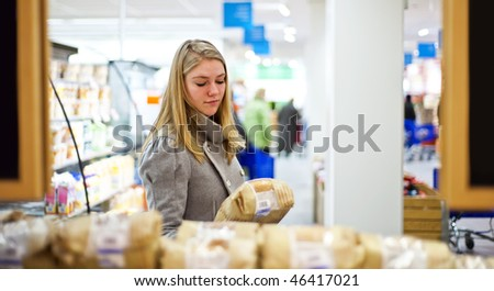 Young woman examining a loaf of bread at a supermarkets' bakery