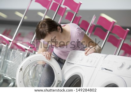 Young woman examining front loader of washing machine in shopping centre - stock photo