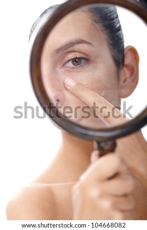 Young woman examining her skin by magnifying glass, looking for blackheads. - stock photo