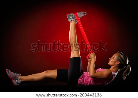 young woman exercise with elastic fitness band in the gym - stock photo