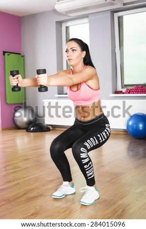 young woman exercises with dumbbells