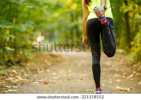 Young woman exercising and stretching muscles before sport activity in park - stock photo