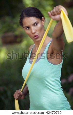 Young woman exercising in outdoor setting. Vertically framed shot. - stock photo