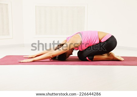 Young woman exercising stretching back yoga pose on the red mat - stock photo