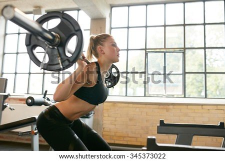 Young woman exercising using barbell with heavy weights in a health club.  Female in sportswear doing squats in gym. - stock photo