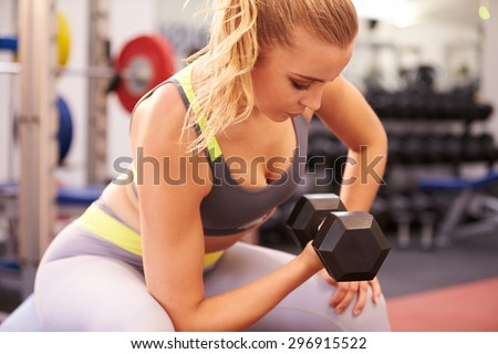 Young woman exercising with dumbbells at a gym, horizontal - stock photo