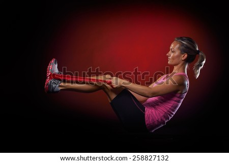 young woman exercising with elastic fitness band in the gym - stock photo