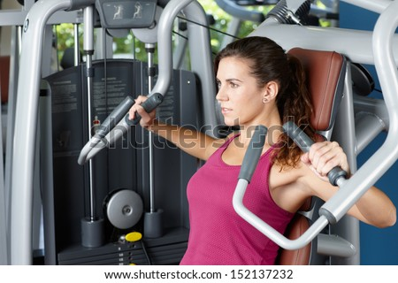 Young woman exercising with machine - stock photo