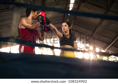 Young woman exercising with trainer at boxe and self defense lesson. Copy space - stock photo