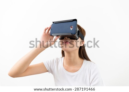 Young woman experience though VR device - stock photo