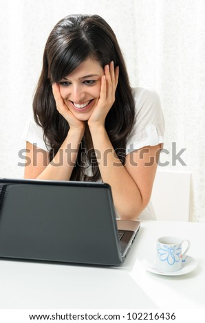Young woman  expresses emotion and looks glad while she lays her head on hands and looks to her laptop screen.