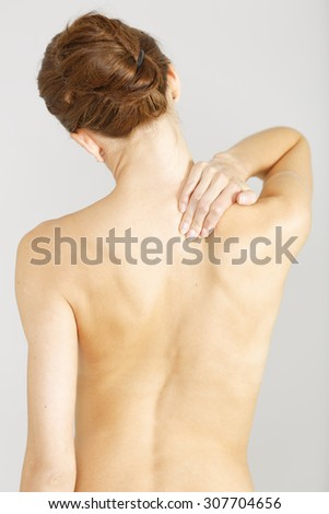 Young woman facing away massaging her neck from an ache or pain
