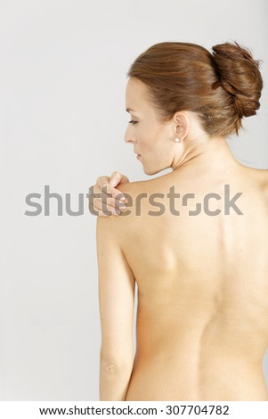 Young woman facing away massaging her shoulder from an ache or pain - stock photo