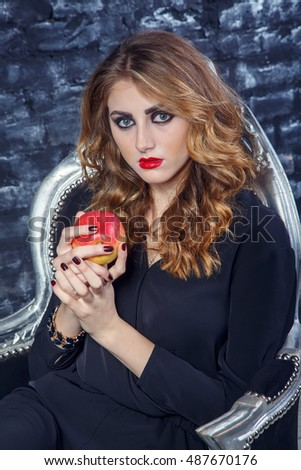 Young woman fashion model holding a red apple.