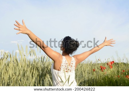 young woman feeling free, rear view - stock photo