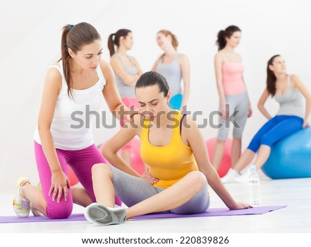 Young woman feeling tired and having pain in her abdomen after aerobics class. - stock photo