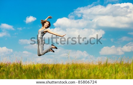 young woman field highly cross-legged jumps - stock photo