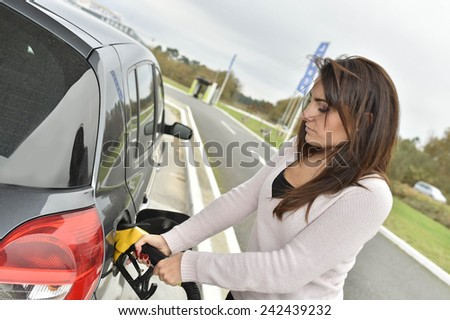 Young woman filling her car tank at gas station - stock photo
