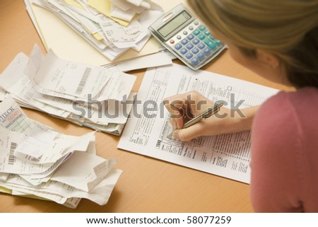 Young woman fills out tax information at her desk with piles of receipts.  Horizontal shot. - stock photo