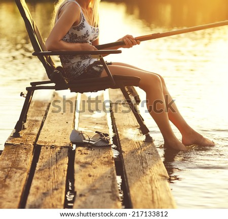 Young woman fishing on a summer sunny evening.  - stock photo