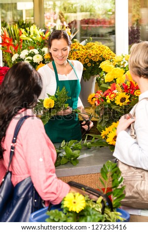 Young woman florist cutting flower shop customers retail colorful - stock photo
