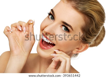 Young woman flossing her teeth. - stock photo