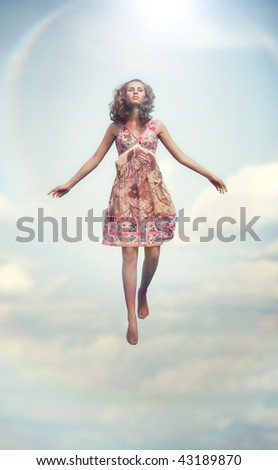 Young woman flying up. Soft colors. - stock photo