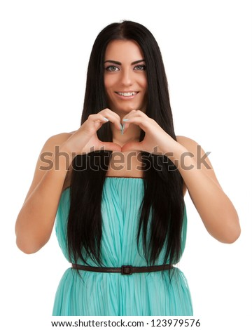 Young woman forming heart shape with hands - stock photo