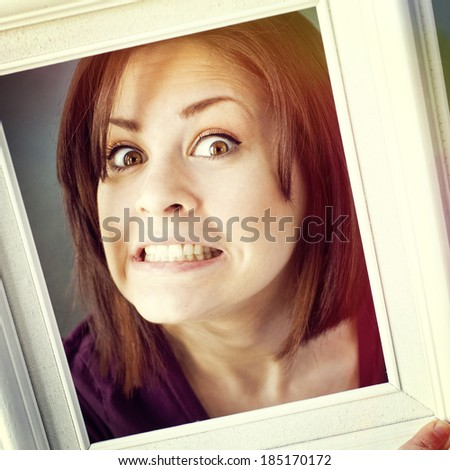 young woman framed by a vintage white photo frame making a silly face, instagram style