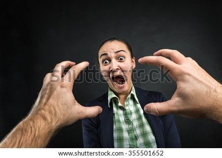 Young woman frightened with huge human hands - stock photo