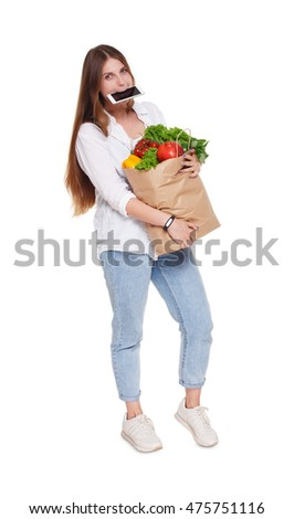 Young woman full length portrait, holds shopping bag full of groceries with mobile in mouth, busy buyer concept, isolated at white background. Healthy food in paper package with vegetables and fruits