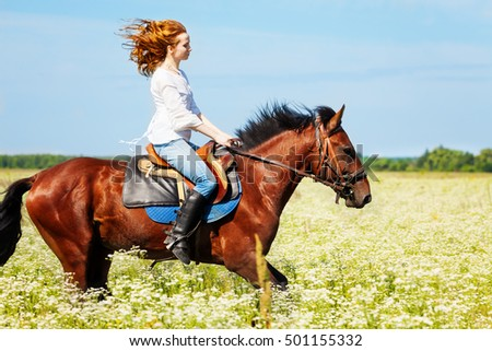 Young woman galloping horseback in flowery meadow